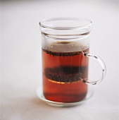 Tee mit Teeblättern im Glas