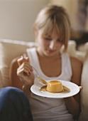 A blonde girl eating pumpkin pudding with caramel sauce