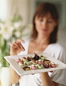 Woman reaching for chocolates on plate