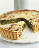 Spinach tart with cherry tomatoes, partly slices