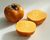 Sharon fruit (Diospyros kaki), whole and halved