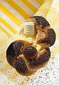 Poppy seed roll, broken open, with butter