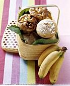 Banana muffins and chocolate & mango muffins in basket, bananas