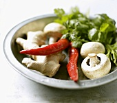 Ginger root, chillies, mushrooms, coriander leaves on plate