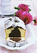 Marble cake with icing sugar, a slice cut