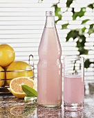 Pink grapefruit lemonade in glass and bottle