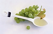 Grape seed oil on spoon beside green grapes
