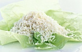 A heap of grated coconut on green paper