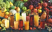 Various types of fruit juice in glasses in front of fresh fruit