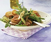 Fried potato salad with sausage and rocket