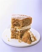 Piece of orange carrot cake with icing sugar, a bite taken