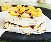 Baisertorte mit Pfirsichen, Preiselbeeren und Pistazien