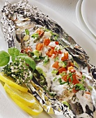 Trout in foil with tomatoes, herbs and sour cream