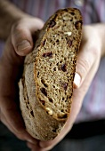 Hands holding nut bread with a piece cut off