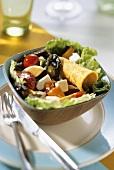 Salad leaves with courgettes, tomatoes, egg, feta and fajita