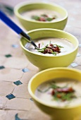 Three bowls of chestnut soup with bacon and chives