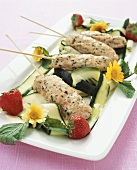 Salmon on sticks with courgettes, strawberries and flowers