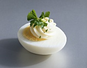 Half a boiled egg with mayonnaise and parsley