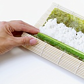 Making maki sushi with cucumber (rolling up bamboo mat)