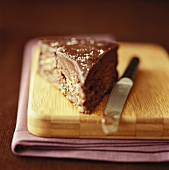 Piece of chocolate cake on chopping board