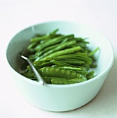 Mangetout and green beans in a white bowl
