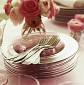 Pile of glass plates & forks on table laid for special occasion