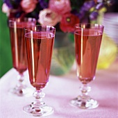 Three glasses of pink sparkling wine in front of flowers
