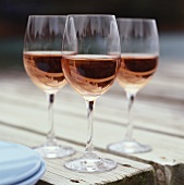 Three glasses of rosé wine on wooden table in the open air