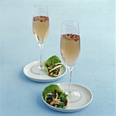 Two pink sparkling wine cocktails and lettuce wraps