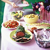 Open-air summer buffet with roast beef and salads