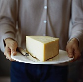 Person serving a wedge of Cheddar cheese on a plate