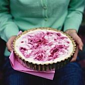 Woman serving raspberry cream tart