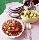 Tomato salad and potatoes with capers on buffet table