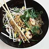 Rice noodles with shrimps and peanuts in a wok