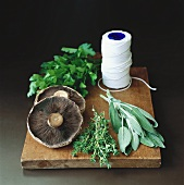 Mushrooms, fresh herbs & kitchen string on chopping board