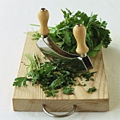 Parsley, partly chopped, with mezzaluna