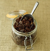 Raisins in a storage jar with a scoop