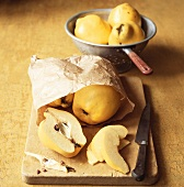 Quinces (whole and sliced) in paper bag on chopping board