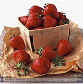 Strawberries in a punnet and beside it on paper