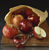 Red apples, whole, halved and apple peel, with paper bag