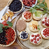 Assorted small sponge cakes with berries and fruit