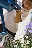 Kind giesst mit blauer Giesskanne Blumen vor dem Haus