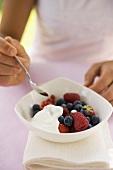 Woman eating fresh berries with yoghurt