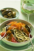 Spaghetti with bresaola and tomatoes, green olives in bowl