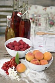 Berries, apricots, sugar & bottles of juice on garden table