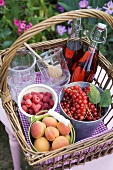 Berries, apricots, bottles of juice and jars in a basket