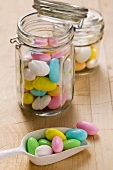 Sugared almonds in storage jars and on scoop