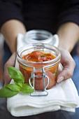 Hände halten Glas mit selbstgemachter Tomatensauce