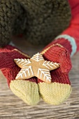 Hands in woollen mittens holding gingerbread star