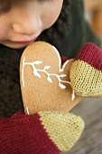 A child in woollen mittens holding a Christmassy gingerbread heart